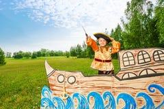 Pojken piratkopierar in dräktställningen på skeppet med svärdet Royaltyfri Fotografi