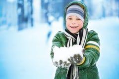 Pojken plaing med snow fotografering för bildbyråer