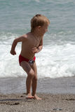 pojken plays sjösidan Arkivfoto