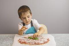 Pojken prepearing pizza fotografering för bildbyråer