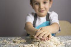 Pojken prepearing pizzadeg royaltyfria bilder
