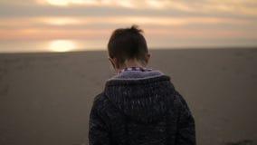 Pojken promenerar stranden på solnedgången stock video