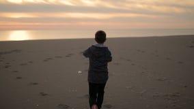 Pojken promenerar stranden på solnedgången lager videofilmer