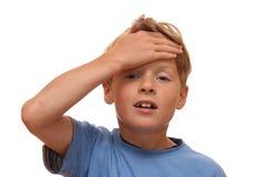 pojken räknar den hans pannan Arkivbild