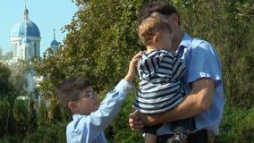 Pojken rätar ut den lilla brodern för kläder arkivfilmer