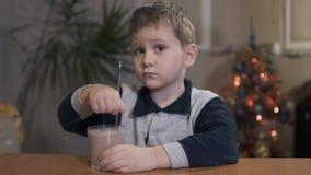 Pojken rör en milkshake vid en sked arkivfilmer