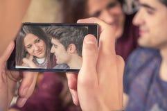 Pojken räcker att ta foto till tonårs- par på soffan Arkivfoto