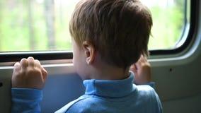 Pojken reser med drevet och ser ut fönstret som håller ögonen på de rörande objekten utanför fönstret Resa med arkivfilmer