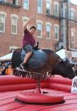 Pojken rider en mekanisk tjur på en mexicansk gatafestival i Chicago royaltyfri bild