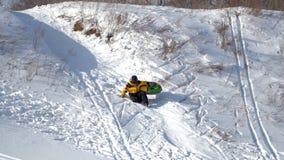 Pojken rullar från ett snöig berg stock video