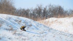 Pojken rullar från ett snöig berg arkivfilmer