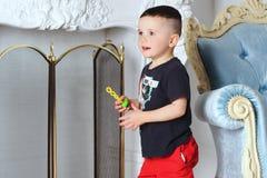 Pojken rymmer en leksak i hans hand arkivbilder