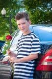 Pojken rymmer en ros nära bilen Begreppet av förälskelse Arkivfoton