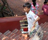 Pojken rymmer fågelburen till salu till filantropet för att köpa en fågel för att släppa på den Phnom templet arkivfoton