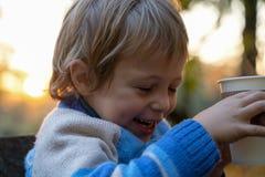 Pojken rymmer koppen i händer på stupad sidabakgrund härlig dag för höstlynne Guld- nedgång i stilleben ljus fall fotografering för bildbyråer