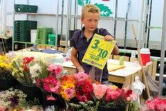 Pojken säljer blommor på bönderna marknadsför Royaltyfri Fotografi