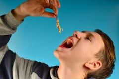 Pojken sätter i hans mun en liten röd ödla på en blå bakgrund i studion royaltyfria foton