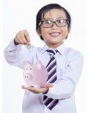 Pojken sätter myntet in i en spargris Royaltyfri Fotografi
