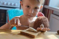 Pojken sätter ost på rostat bröd Arkivfoto