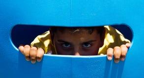 Pojken ser från baksidan av ett plast- fönster arkivfoton