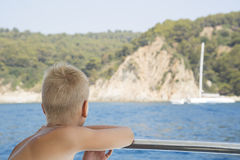 Pojken ser från fartyget på havet Fotografering för Bildbyråer