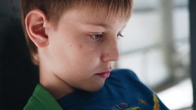 Pojken ser hänsynsfullt på skärmen av smartphonen Pojken sitter under bron close upp sinnesr?relser stock video