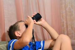 Pojken ser i en monokel royaltyfri fotografi