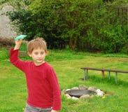 Pojken ser kameran, innan han kastar ett pappers- flygplan Arkivbilder