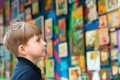 Pojken ser målningarna på utställningen av bildmässig konst och kreativitet royaltyfri fotografi