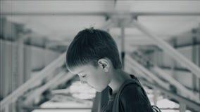Pojken ser ner känslomässigt medan under bron över vattnet Svartvita ramar stock video