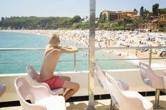 Pojken ser stranden från fartygets däck Royaltyfria Foton