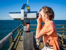 Pojken ser till och med ett binokulärt på havet royaltyfria bilder