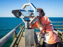 Pojken ser till och med ett binokulärt på havet arkivfoton