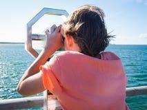 Pojken ser till och med ett binokulärt på havet arkivbilder