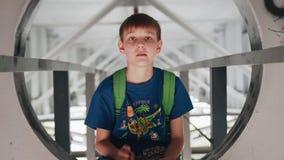 Pojken ser upp på kameran och visar ett tecken av fred Pojkeleendena Det lokaliseras under bron på metallstrukturer stock video