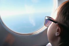 Pojken ser ut fönstret av nivån i solglasögon arkivfoton