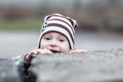 Pojken ser ut från under stenen royaltyfri fotografi