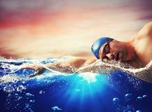 Pojken simmar i ett blått djupt vatten Arkivbild