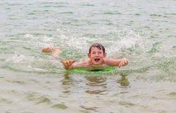 Pojken simmar i havet med hans boogiebräde Arkivbilder