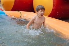 Pojken simmar i pölen Arkivfoto