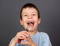 Pojken simulerar tandborttagning med plattång Royaltyfria Foton