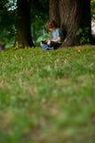 Pojken sitter efter att ha korsat ben nära ett stort träd parkerar in Royaltyfria Foton