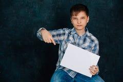 Pojken sitter, ett rent ark, i studion Royaltyfri Bild