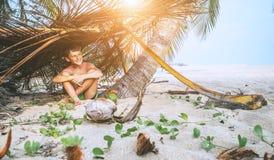 Pojken sitter i selfmade koja p? den tropiska stranden och spelar i Robinzone royaltyfria foton