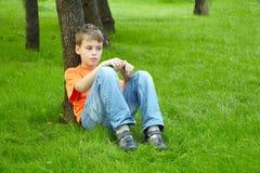 Pojken sitter med den fundersama framsidan på gräs Royaltyfri Bild