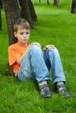 Pojken sitter med den fundersama framsidan på gräs Royaltyfria Bilder