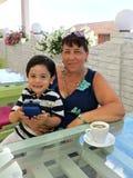 Pojken sitter med hans farmor i utomhus- kafé på sommardagen Royaltyfria Bilder