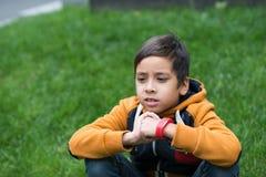 Pojken sitter på en gräsmatta och tänker Royaltyfri Foto