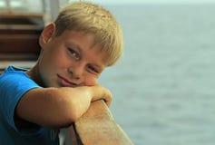 Pojken sitter på en plats i färja arkivfoto
