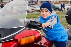Pojken sitter på en röd motorcykel royaltyfri bild